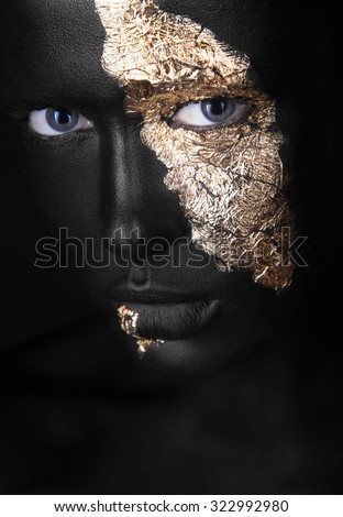 fashion portrait of a dark-skinned girl with gold make-up.Beauty face. Picture taken in the studio on a black background. - stock photo