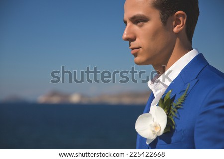 Fashion portrait of a handsome groom in blue suit - stock photo