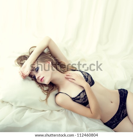 Fashion portrait of a sensual girl sleeping in white bed - stock photo