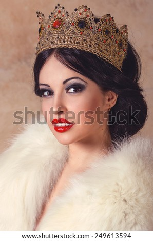Fashion portrait of a sexy brunette model in golden vintage queen crown and white fur coat - stock photo