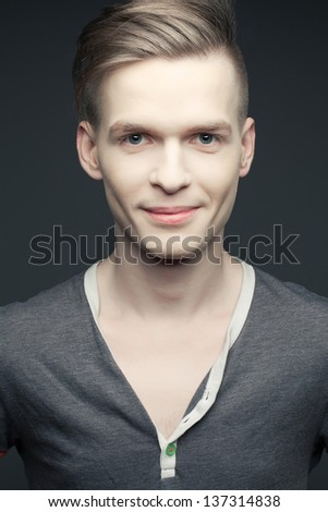 Fashion portrait of a smiling elegant young and handsome man posing over gray background. Perfect skin and hair. Close up. Studio shot - stock photo