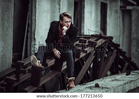 fashion portrait of a stylish man posing outside, autumn time, sitting on old constructions - stock photo