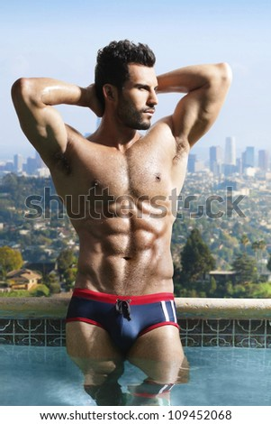 Fashion portrait of a very muscular sexy man in luxury scenic swimming pool - stock photo