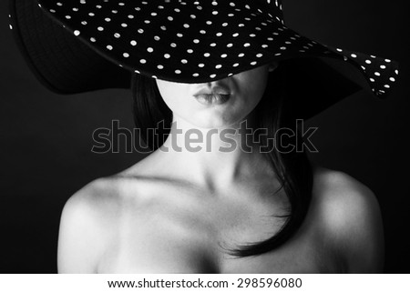 Fashion portrait of a woman with lock hair and  black and white dots hat and pout lips - stock photo