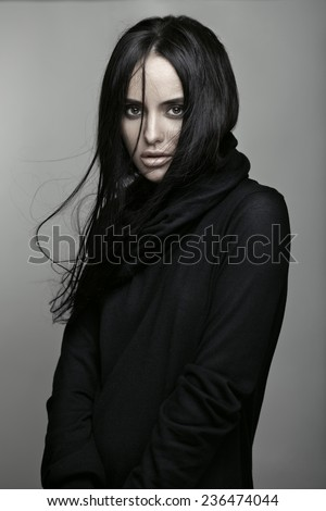Fashion portrait of a young beautiful brunette girl with long black straight flying hair. Magnificent hair. Black roll neck jumper. - stock photo