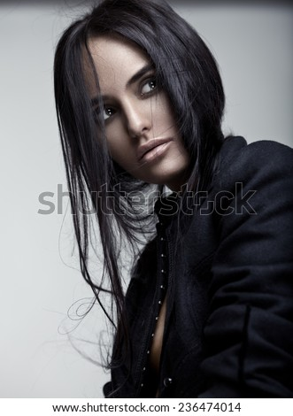 Fashion portrait of a young beautiful brunette girl with long black straight hair. - stock photo