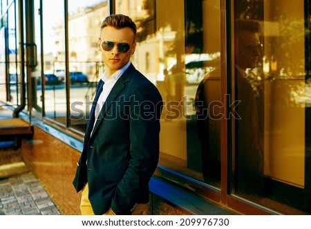 Fashion portrait of a young casual man looking away from the camera. Street photo. Copy-space. - stock photo