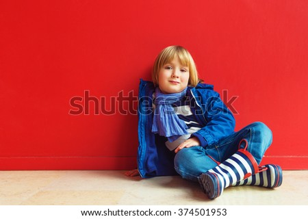 Fashion portrait of adorable little boy of 4-5 years old, wearing blue jacket, scarf and stripes rain boots, sitting on the floor against bright red wall