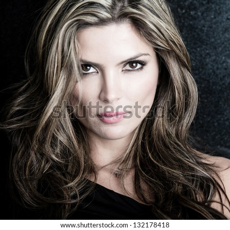 Fashion portrait of an attractive woman over dark background