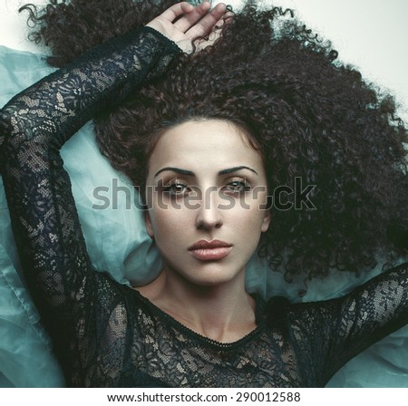 Fashion portrait of attractive brunette girl with curly hair in black dress. Lying on back. - stock photo