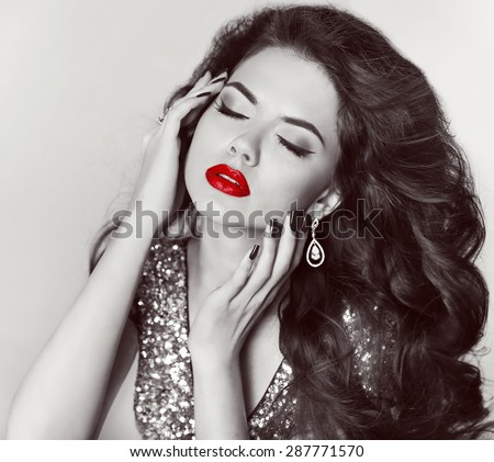 Fashion portrait of attractive girl model with red lips and jewelry. Long wavy hair. Black and white photo.