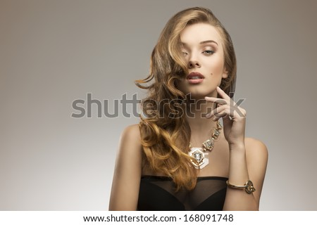 fashion portrait of attractive young girl with elegant wavy hair-style, sexy dress and big golden necklace   - stock photo
