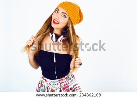 Fashion portrait of beautiful blonde dj hipster girl holding her hairs , wearing bright sexy outfit and big white earphones. White background, not isolated.