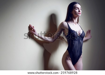 Fashion portrait of beautiful brunette woman. Sexy young woman in sexy black lingerie. - stock photo