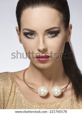 fashion portrait of beautiful brunette woman with long smooth hair, stylish make-up, golden dress and big necklace  - stock photo