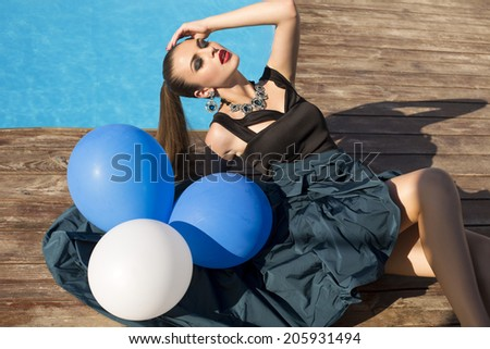 fashion portrait of beautiful glamour young woman in elegant dress and bijou with white and blue balloons lying beside a swimming pool - stock photo