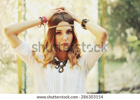 Fashion portrait of beautiful hippie young woman wearing boho chic clothes and summer hat outdoors. Soft warm vintage color tone. Artsy bohemian style. - stock photo