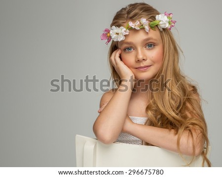 Fashion portrait of beautiful little girl with wreath