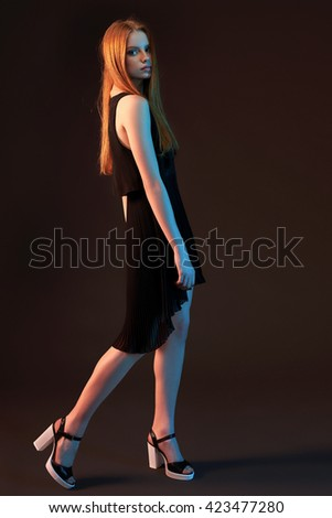 Fashion portrait of beautiful red haired fashion model girl with long  hair in black dress posing in full length over dark background - stock photo