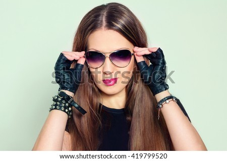 Fashion portrait of beautiful rock style brunette young woman in sunglasses, leather bracelets and gloves, bright makeup
