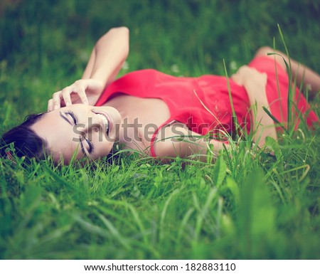 fashion portrait of beautiful sexy female brunette girl model lying in green summer bright grass in the park with makeup in red dress.perfect skin.nature - stock photo