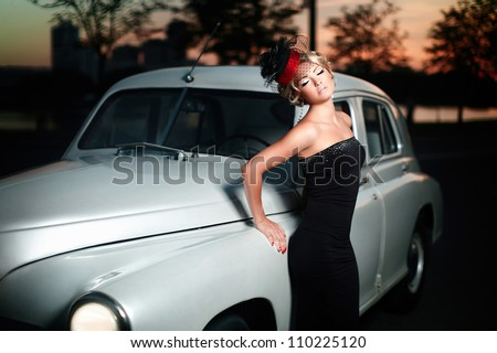 fashion portrait of beautiful sexy woman model girl posing standing near car in retro style with bright makeup at sunset - stock photo