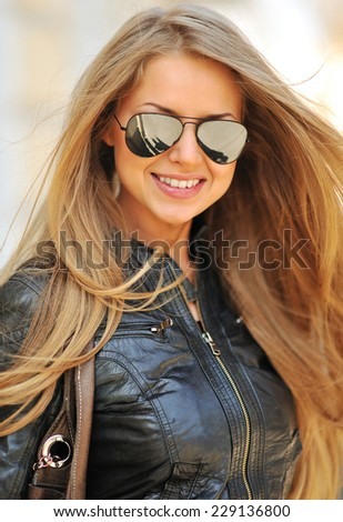 Fashion portrait of beautiful smiling woman wearing sunglasses - close up  - stock photo