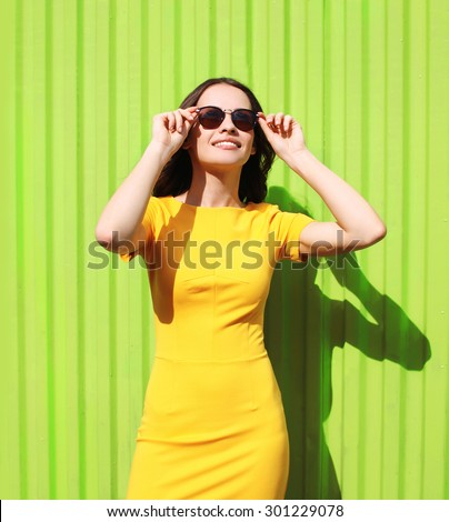 Fashion portrait of beautiful smiling young woman in yellow dress and sunglasses against the colorful green wall - stock photo