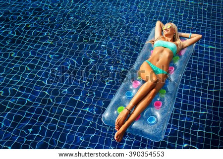 Fashion portrait of beautiful tanned woman with blond hair in elegant bikini relaxing on a swimming pool