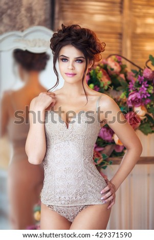 Fashion portrait of beautiful woman in beige lingerie