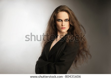 Fashion portrait of beautiful woman in black. Young attractive looking woman with long thick hair.