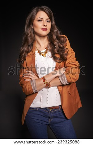 Fashion portrait of beautiful woman in jeans and jacket posing over dark studio background - stock photo
