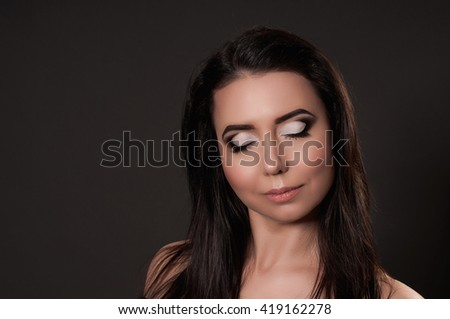 Fashion portrait of beautiful woman with makeup on dark backgroun