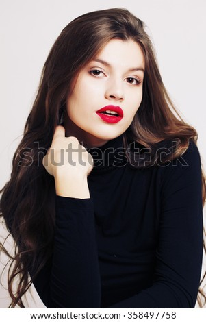 Fashion portrait of beautiful young brunette woman in a turtleneck. Make-up and cosmetics. Beautiful model girl makeup. Perfect skin. Professional make up. Red lips - stock photo