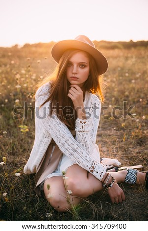 Fashion portrait of beautiful young pretty girl with hippie outfit and hat outdoors in the field at sunset. Soft warm color tone. Boho lifestyle. Bohemian Style. Vertical with blank space for text - stock photo