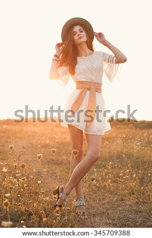 Fashion portrait of beautiful young pretty girl with hippie outfit and hat standing in the field at sunset. Soft warm color tone. Boho lifestyle. Bohemian Style. Vertical with blank space for text - stock photo