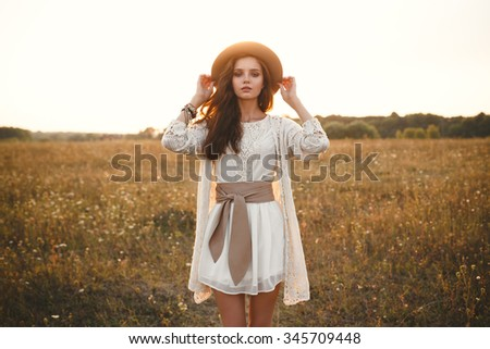 Fashion portrait of beautiful young pretty girl with hippie outfit holding hat outdoors at sunset. Soft warm vintage color tone. Boho lifestyle. Bohemian Style. Horizontal with blank space for text - stock photo