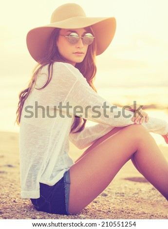 Fashion portrait of beautiful young woman on the beach at sunset, bright warm sunny color tones - stock photo