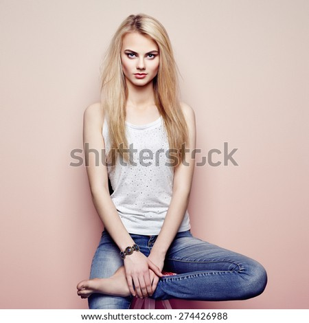 Fashion portrait of beautiful young woman with blond hair. Girl in blouse and jeans. Jewelry and hairstyle - stock photo