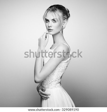 Fashion portrait of beautiful young woman with blond hair. Girl in white dress on white background - stock photo