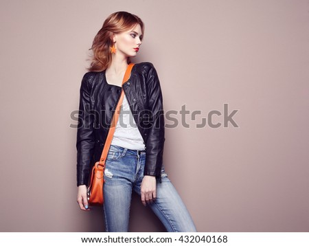 Fashion portrait of beautiful young woman with red hair. Girl in blouse and jeans. Jewelry and hairstyle. Girl with handbag - stock photo