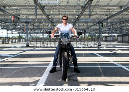 Fashion portrait of biker man wearing a white shirt, blue jeans and sunglasses sitting on his classic motorcycle in a empty car parking - stock photo