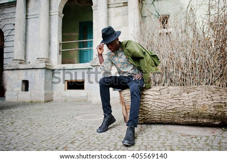 Fashion portrait of black african american man on green velvet jacket at his shoulders and black hat, sitting at felled tree background old vintage house with arch and columns