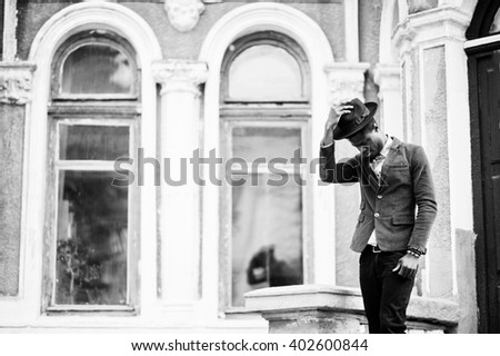 Fashion portrait of black african american man on green velvet jacket stay on stairs and wear his black hat background old mansion. B&W photo