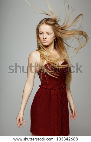 Fashion portrait of blond fashion model posing with hair fluttering in the wind
