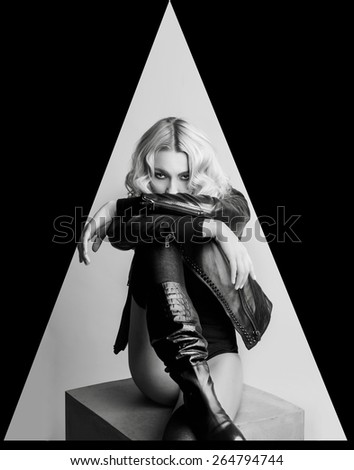 Fashion portrait of blond woman in leather jacket and boots. Vogue style. Monochrome. - stock photo