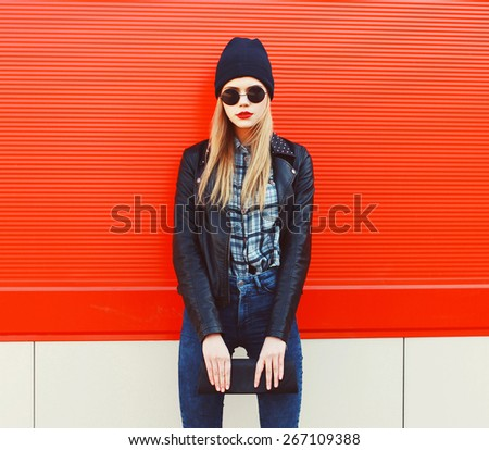 Fashion portrait of blonde girl in rock black style, wearing a sunglasses and leather jacket standing outdoors against the red urban wall in the city  - stock photo