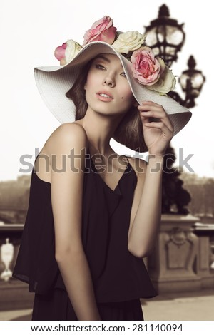 fashion portrait of brunette woman with romantic spring style, wearing black dress and floral big hat with some colorful roses. Sensual expression.  - stock photo