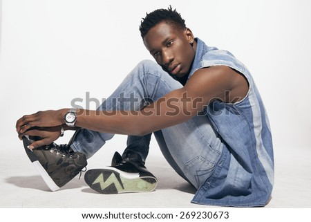fashion portrait of casual young african man standing on white background