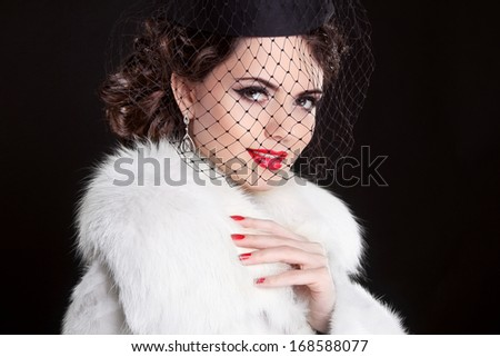 Fashion Portrait of elegant retro woman wearing little hat with veil and white fur coat
